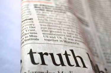 news paper with the word truth in large writing