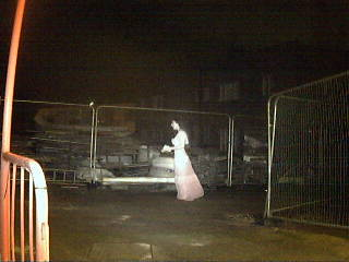 """The Limitless Security """"ghost"""". A night time image of a building yard shows a ghostly woman wearing a full length dress. Her skin and the dress are similar shades of eery white and her hair is dark."""