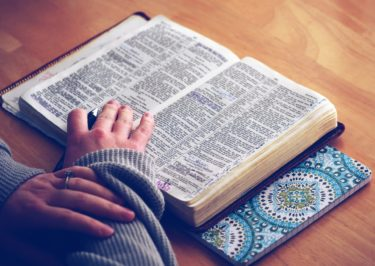 Feminine hands held over a bible, with a pen in one hand as if studying.