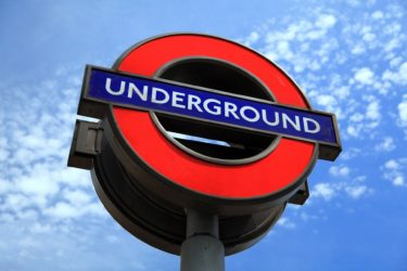 A photo of the London Underground signage against a blue sky backdrop