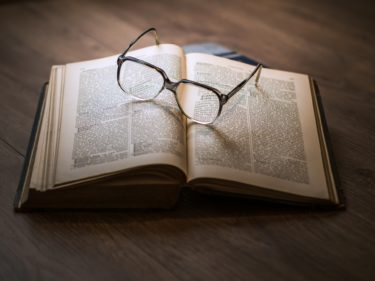 An open book with glasses resting on the page