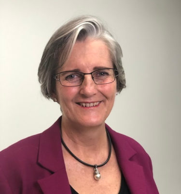 Dr Joy Bowles. She is smiling and has a cool short hair cut with highlights of silvery grey through the front. She is wearing metal framed glasses, a chunky black necklace and a dark magenta blazer. Image source: https://www.ejoybowles.com/bio.html#/