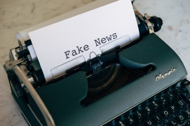 """A type-writer and paper - the words on the paper read """"Fake News!"""""""