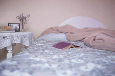 A bed in a soft pink room with grey sheets and a white table beside it. A pink book lays open on the bed.