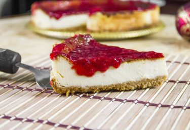 A slice of strawberry topped cheesecake
