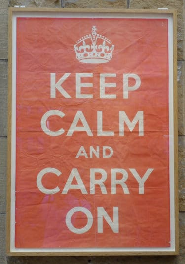 "A red poster with white writing that reads ""Keep Calm and Carry On"""