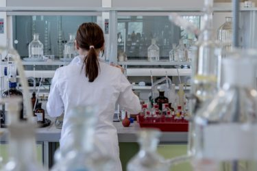 A woman from behind as she stands in a lab wearing a lab coat