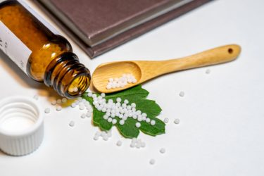 A bottle of homeopathy, open with pills spread across a leaf and onto a table top. There is a wooden spoon and a book beside the bottle and pills.