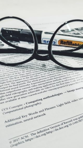 An academic paper with a pair of glasses resting on top.