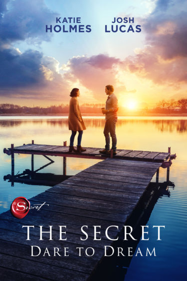 The Secret Dare to Dream promo image. Katie Holmes and Josh Lucas stand on a jetty over a lake with a sunset behind them.