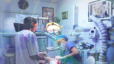 A dentist and her assistant work on a patient's teeth