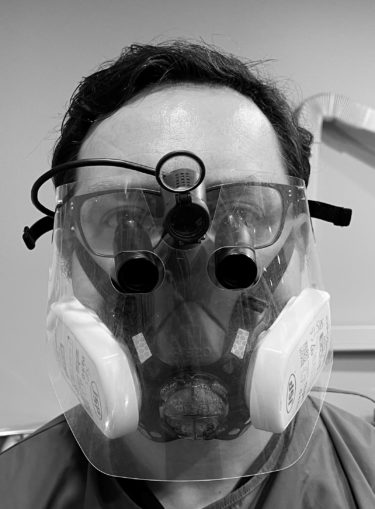Shaun is wearing a high filtration face mask and visor. The face mask includes two large filter packs on either side and straps that cross the cheeks, over the ears and around the back of the head. Between his regular glasses and the visor are a pair of dental magnifying loupes and above, a small head torch. The only part of Shaun's skin that is clearly visible is his forehead.