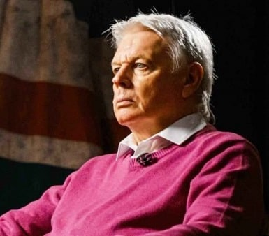 David Icke wearing a pink jumper and white shirt. He has a small microphone clipped to his jumper.