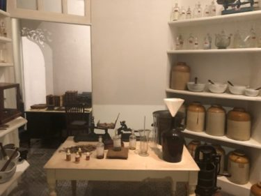 The first homeopathy pharmacy in Brazil, which was gifted to Brazil's national museum - many shelves with jars and bottles stand behind a table laden with small bottles as if ready to be filled.