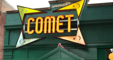 "The store front of Comet Ping Pong, the pizza place at the centre of the Pizzagate conspiracy theory. The store is painted dark green and has the word ""comet"" written in lighted yellow letters. Image by DOCLVHUGO [CC-by-4.0]"