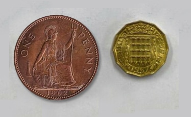 A penny along side a thrupenny - the penny, though much larger, is worth three times less than the thrupenny.