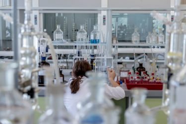 A scientist working in a laboratory. She is wearing a white labcoat and holding a pipette.