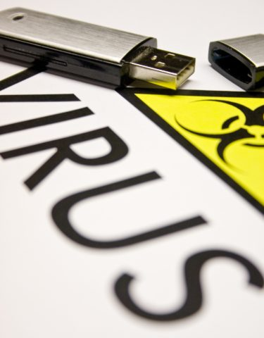 A sheet of white paper with the word Virus and a yellow triangle with a biohazard symbol on it. There is a USB pen sitting on top of the paper.