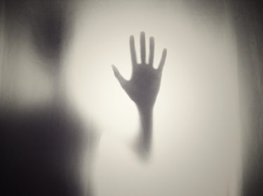 A shadowy figure holding their palm out