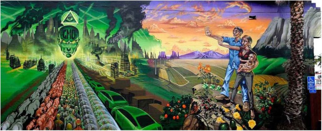 """On the left half of the mural is a dystopian landscape with lines of animals, humans, and machines all converging towards a smoking skyline centered around a giant floating head with """"GMO"""" printed on the forehead and an Eye of Providence floating over the heat. On the right side of the mural is a native family, man woman and baby, standing in a verdant utopia with their arms stretched out in a stop sign"""
