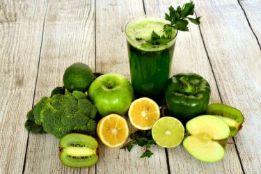 A green smoothie and lots of green fruit and vegetables