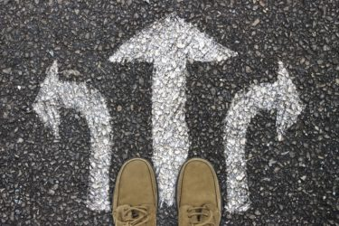 A person stands at three directional arrows drawn with chalk on the floor.