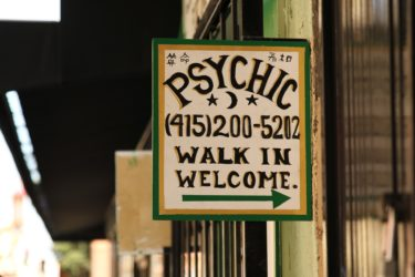 """Advert for a Psychic that reads """"Psychic"""" a phone number and the words """"walk in welcome"""" with an arrow."""