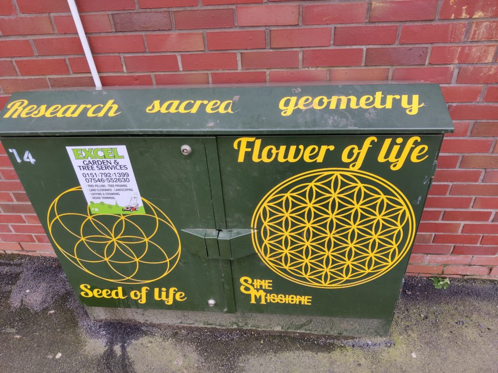 """A metal box with Sine Missione artwork on it - the words """"research sacred geometry"""", """"flower of life"""", """"seed of life"""" and two geometric patterns are seen in yellow. One of the patterns is partially covered by an unrelated advert for gardening services."""