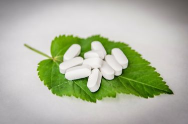White tablets sitting on top of a nettle leaf