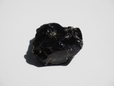 An obsidian crystal on a white background