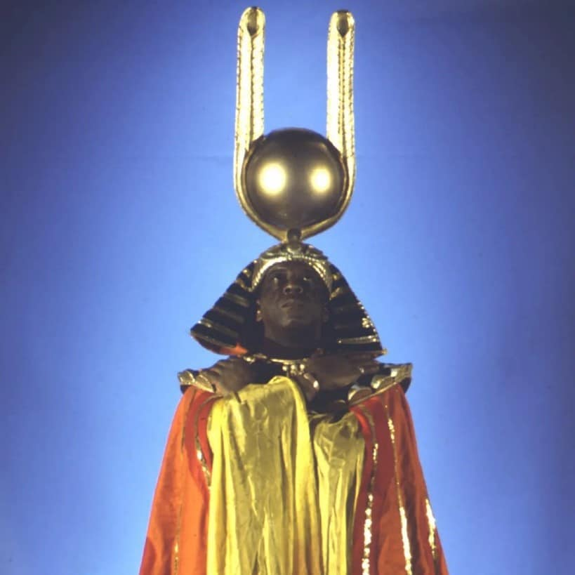 An image of Sun Ra. He is a black man wearing a red and yellow gown with gold detailing. The shoulders have large shoulder pads with gold detailing. On his head, Sun Ra wears an ancient Egyptian style headdress with a large gold ball on the top of it similar to that of the ancient Egyptian god, Ra. He is looking up to the sun shaped ball and has his arms across his chest.