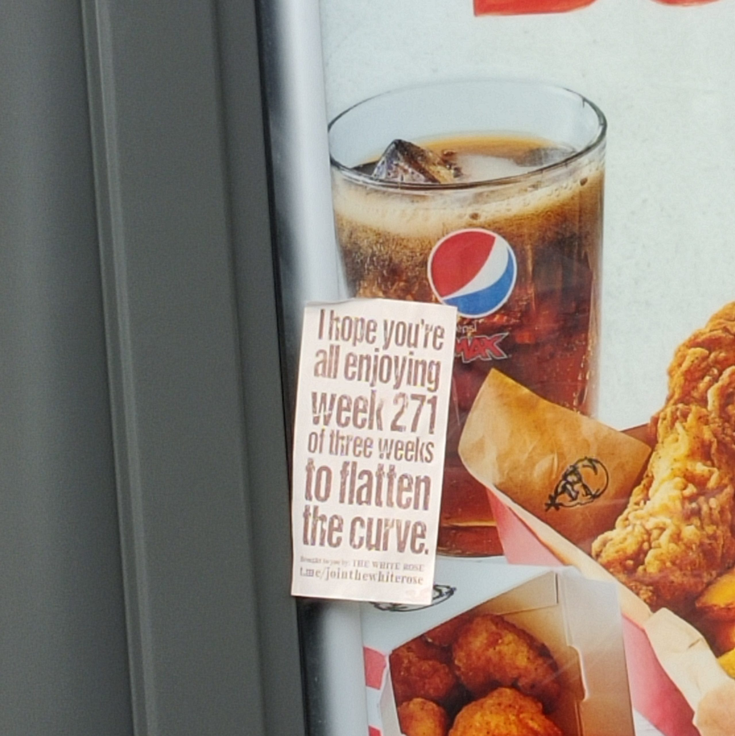 """A White Rose sticker on a bus stop advert for fried chicken. The sticker reads """"I hope you're all enjoying week 271 of three weeks to flatten the curve"""" - in small print below are adverts for the White Rose Telegram group."""