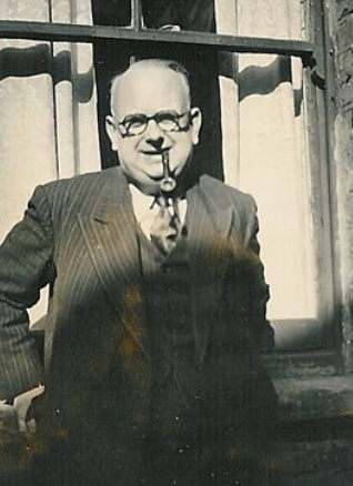 Harold 'Chib' Chibbett (1900-1978) - a black and white photo of a balding man with whisps of white hair, dark rimmed glasses and a pipe. He's standing in front of a window, outside, with his hands on the window ledge and he's wearing a three piece suit with a shirt and tie.