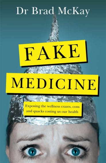 """The cover of Dr Brad McKay's book: Fake Medicine. The cover has a blue gradient background with a photo of a worried looking person wearing black eye make up and a tin foil hat. Over the top of the photo is black text on a yellow box background with the words """"Fake Medicine"""" and """"Exposing the wellness crazes, cons and quacks costing us our health""""."""