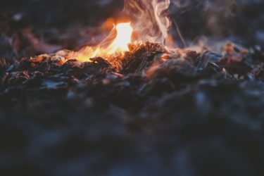 A smouldering fire nearing the end of its life leaving a pile of ash