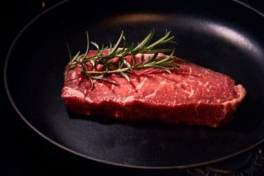 Beef, in a saucepan, with some rosemary.