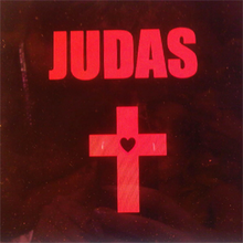 The cover of Lady Gaga's Judas - a dark background with the word JUDAS in large red writing. Beneath is a red cross with a heart in the centre.