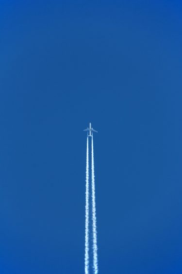 A plane flying on a blue sky with two white contrails following it