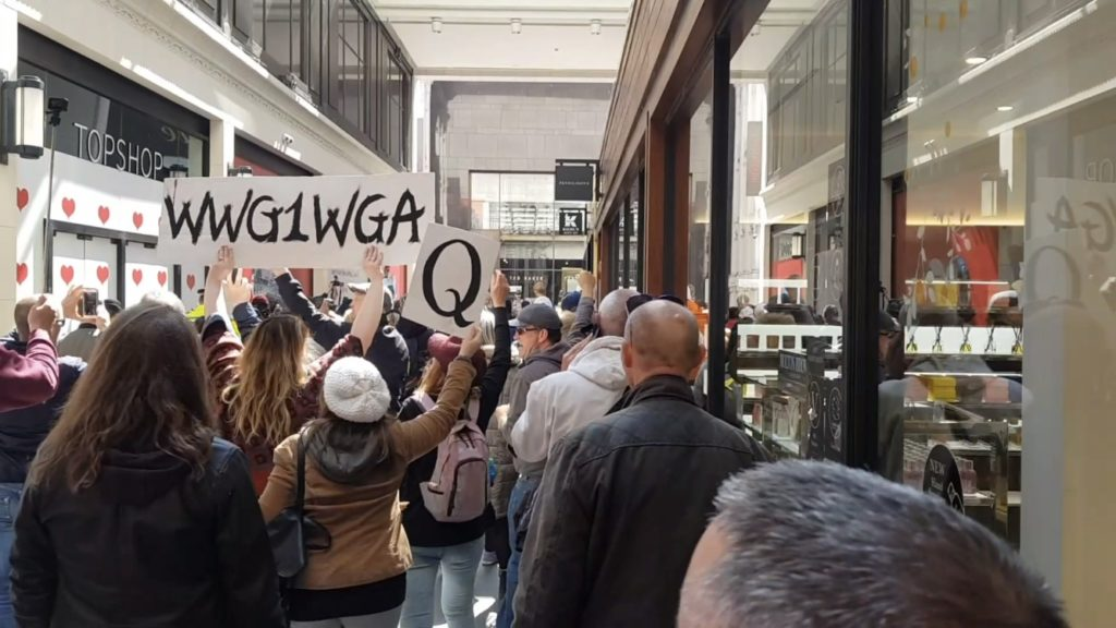 """in a covered shopping street in Liverpool city centre a group of people walk - two women hold aloft signs that read """"WWG1WGA"""" and """"Q"""""""
