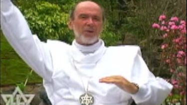 Rael wearing a white outfit with a metal necklace with a Rael symbol