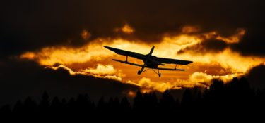 A plane flying into a sunset