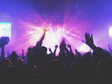 A modern day concert - lights in pinks and purples shine from the stage. The image is taken from the perspective of an audience member looking through a sea of silhouetted hands against the pinky purple light