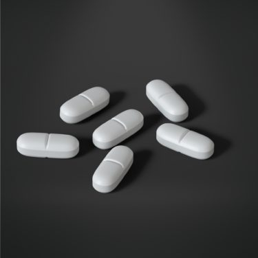 six white tablets on a grey background