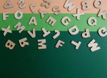 Wooden cut out letters on a green and orange background