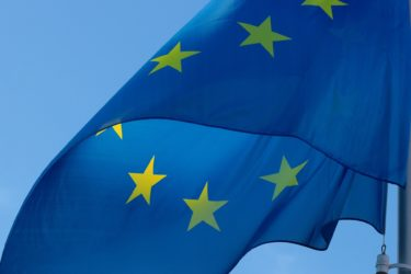 An EU flag - blue with yellow stars in a circle - fluttering in the sky.
