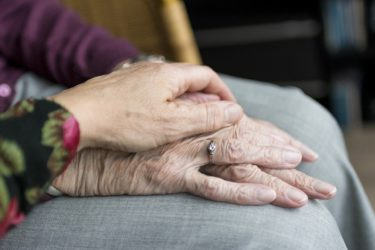 A close up of two pairs of hands. The hands appear to belong to two women, the younger woman's hands are reassuringly held over the top of the older woman's hands.