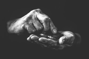 Two hands holding coins as if counting them