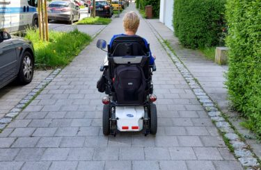 A white woman with a short blonde hairstyle travels down a pavement using her electric wheelchair.